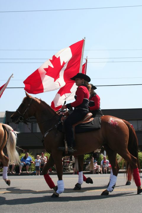 Horseback riders with Canadian flag