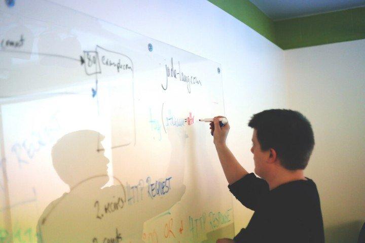 man writing at whiteboard