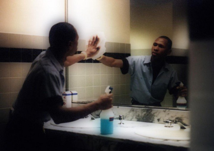 janitor cleaning a mirror