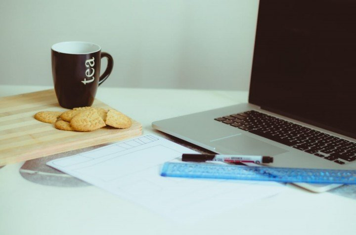 laptop witha cup of tea and crackers