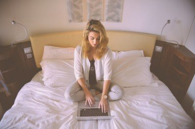 woman using laptop on hotel bed