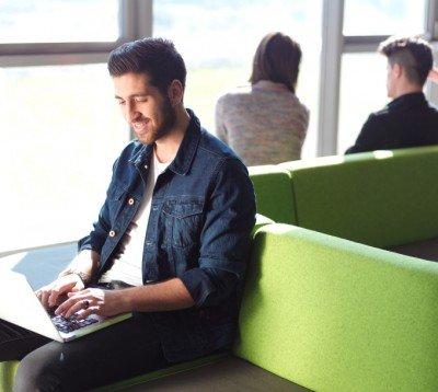 man working on laptop in public