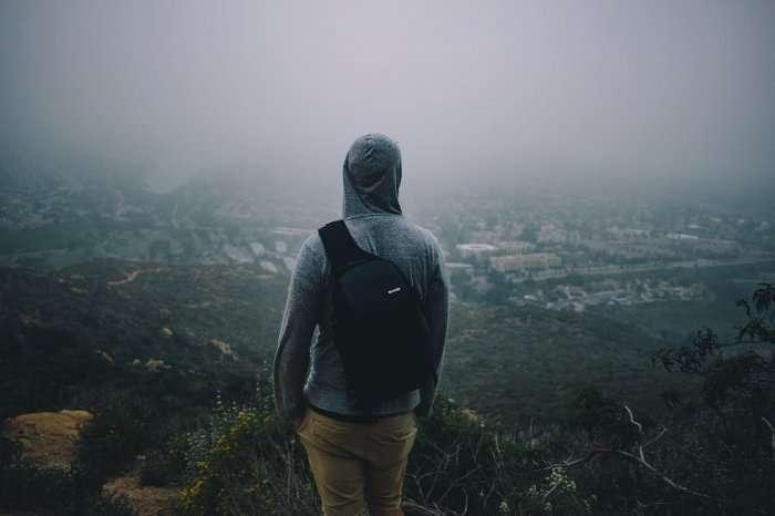 Hooded Man With Backpack Looking Over Horizon Employee