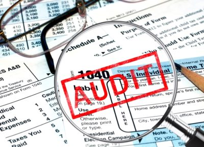 Audit in red with tax forms in background