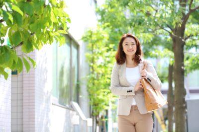 smiling woman walking down the street