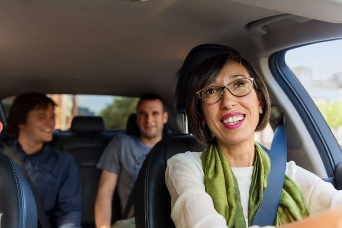 Smiling Uber driver with two passengers