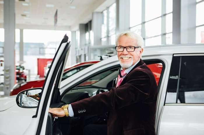 Smiling older driver at auto dealership